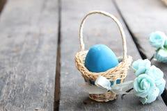 Пасхальное яйцо пасхального яйца в корзине на деревенской таблице Стоковое Фото