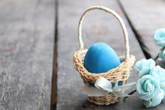 Пасхальное яйцо пасхального яйца в корзине на деревенской таблице Стоковое фото RF
