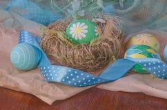 Пасхальные яйца в гнезде и snowdrops Стоковое Изображение