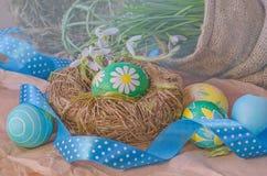Пасхальные яйца в гнезде и snowdrops Стоковая Фотография RF