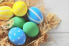 Пасхальные яйца в гнезде на деревенской белой предпосылке стоковые фотографии rf