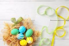 Пасхальные яйца в гнезде на деревенской белой предпосылке стоковое изображение