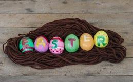 Пасхальные яйца в гнезде на деревянном стоковые фотографии rf