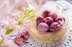 Пасхальные яйца в гнезде на свете - пинк или белизна Стоковая Фотография