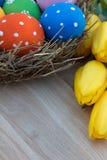 Пасхальные яйца в гнезде на таблице с желтыми тюльпанами Стоковая Фотография