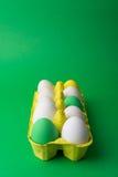 Пасхальные яйца в желтой коробке на зеленой предпосылке Стоковое Фото