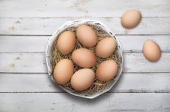 Пасхальные яйца в корзине на белой деревянной предпосылке стоковые изображения