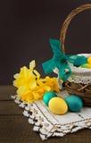 Пасхальные яйца в корзине на деревянном столе с букетом daffodil Стоковая Фотография