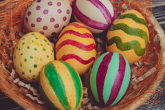 Пасхальные яйца в корзине на деревянных досках Стоковое Изображение