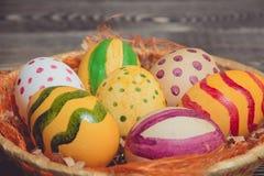 Пасхальные яйца в корзине на деревянных досках Стоковая Фотография RF