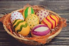 Пасхальные яйца в корзине на деревянных досках Стоковая Фотография