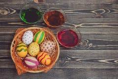 Пасхальные яйца в корзине на деревянных досках Стоковые Изображения