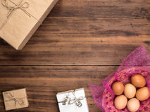 Пасхальные яйца в корзине на предпосылке деревянного стола от старых доск с подарочными коробками, взгляд сверху Стоковые Фотографии RF