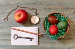 Пасхальные яйца в корзине, яблоке и карманном вахте стоковое фото rf