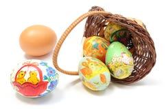 Пасхальные яйца в переворачиванной плетеной корзине Стоковые Фото