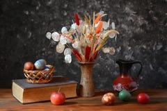 Пасхальные яйца в плетеных корзинах и цветках Стоковые Изображения