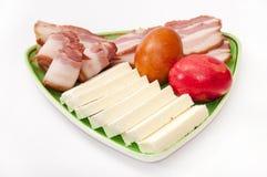 Пасхальные яйца и аранжированный сыр бекона и фета на зеленой плите Стоковое Изображение