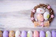 Пасхальные яйца и гнездо на серой деревянной предпосылке Стоковое Изображение