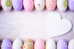 Пасхальные яйца и деревянное сердце на серой деревянной предпосылке Стоковые Фотографии RF