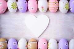 Пасхальные яйца и деревянное сердце на серой деревянной предпосылке Стоковая Фотография RF