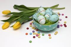 Пасхальные яйца и желтые тюльпаны Стоковая Фотография