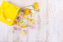 Пасхальные яйца и цветки над белым деревянным столом Стоковая Фотография