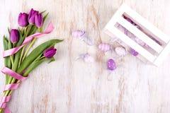 Пасхальные яйца и цветки над белым деревянным столом Стоковое Изображение