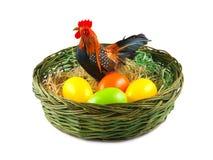 Пасхальные яйца и цыпленок в корзине на белой предпосылке Стоковое Изображение RF
