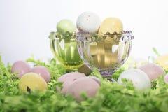 Пасхальные яйца конфеты на кровати бумаги Crepe и в розовом и зеленом Cr Стоковые Изображения RF