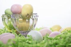 Пасхальные яйца конфеты на кровати бумаги Crepe и в розовом и зеленом Cr Стоковая Фотография