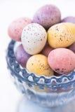 Пасхальные яйца конфеты шоколада в пастельных цветах в голубой кристаллической чашке, крупном плане Стоковое Изображение