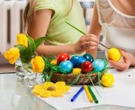 Пасхальные яйца краски рук детей дома Стоковая Фотография