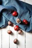 Пасхальные яйца на голубой предпосылке задрапированной тканью Стоковое Фото