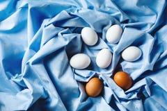 Пасхальные яйца на голубой предпосылке задрапированной тканью Стоковая Фотография
