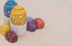 Пасхальные яйца на стойке с cream предпосылкой Стоковое Изображение