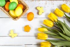 Пасхальные яйца, домодельные печенья и желтые тюльпаны над светлой предпосылкой с космосом экземпляра Стоковое Фото