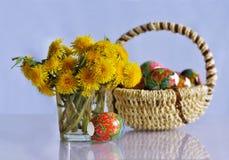 Пасхальные яйца одуванчиков и в корзине. Стоковое Изображение