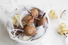 Пасхальные яйца украшенные с пер на белом деревянном шаре стоковое фото