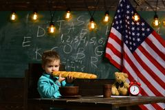 Патриотизм и свобода Обучите ребенк на уроке в 4-ое -го июль Назад к школе или домашнему обучению Мальчик ест хлеб на стоковые фотографии rf