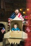 Патриотизм и свобода патриотизм отца и малого ребенка с американским флагом на бумажной ракете на День независимости  стоковое изображение rf