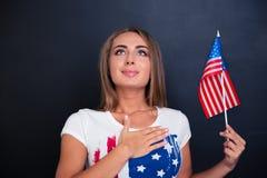 Патриотическая женщина держа флаг США и смотря вверх Стоковая Фотография