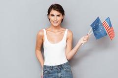 Патриотическая счастливая женщина держа европейца и флагов США Стоковая Фотография