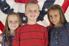 Патриотические дети стоя перед знаменем флага Стоковая Фотография