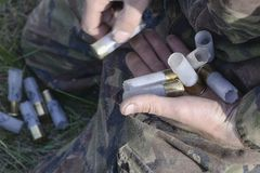 Патроны в руках охотника в маскировочном костюме стоковая фотография