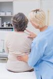 Пациенты медсестры рассматривая назад в клинике Стоковые Фото