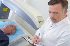 Пациент диаграммы доктора рассматривая около для того чтобы иметь развертку mri Стоковые Изображения