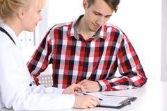 Пациент доктора и мужчины сидя на столе Концепция медицины и здравоохранения Стоковая Фотография