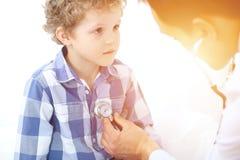 Пациент доктора и ребенка Врач рассматривает мальчика стетоскопом Концепция терапией ` s медицины и детей Стоковое Фото