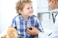 Пациент доктора и ребенка Врач рассматривает мальчика стетоскопом Концепция терапией ` s медицины и детей Стоковое Изображение RF