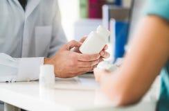 Пациент доктора советуя с о правом лекарстве Врач держа медицину и таблетки в руке стоковые изображения